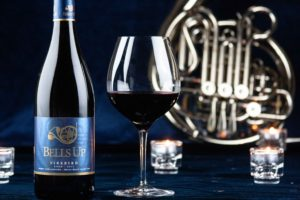 red wine in glass with candles and French horn